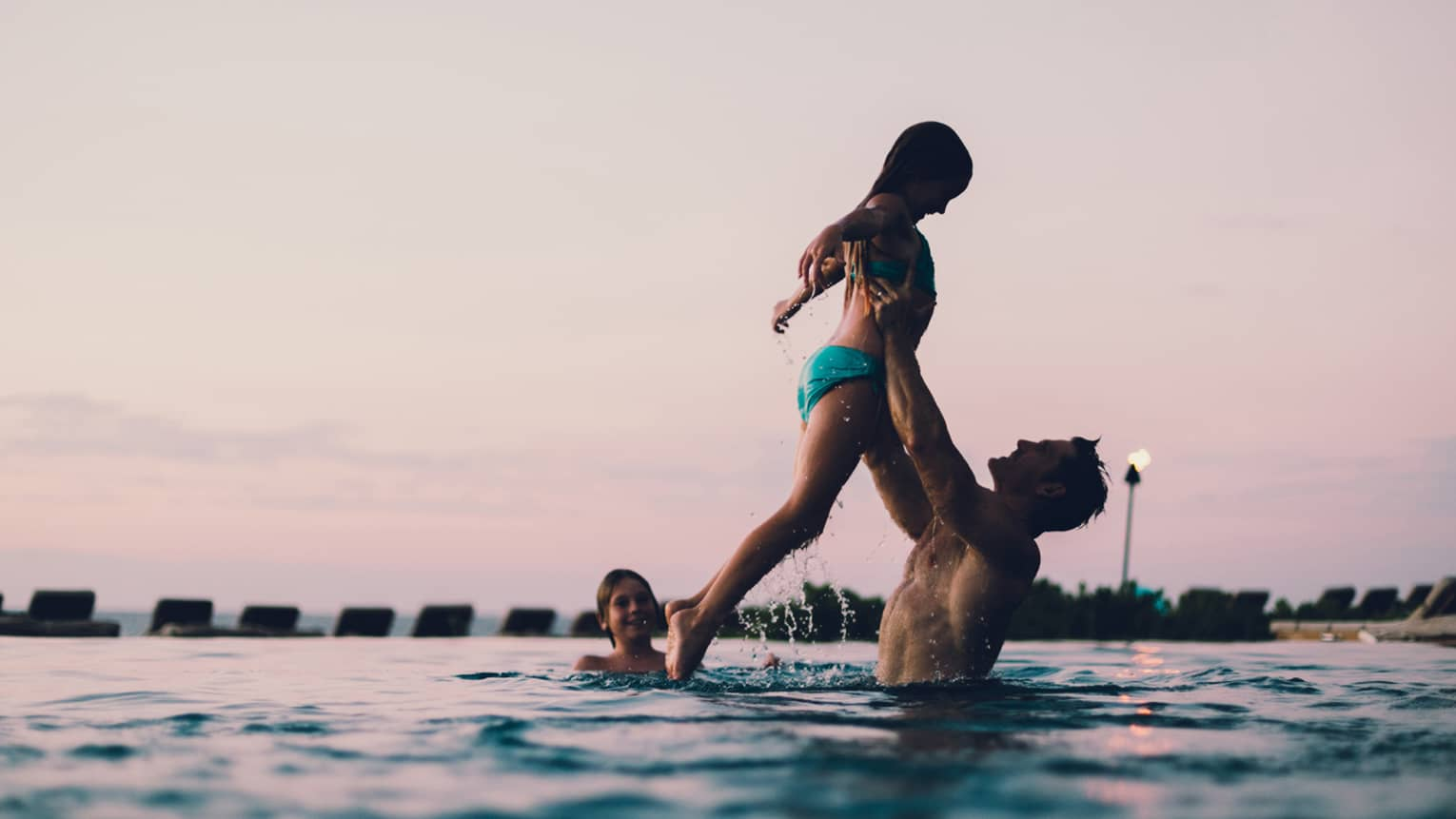Dad lifts daughter in outdoor swimming pool as smiling boy watches, sunset