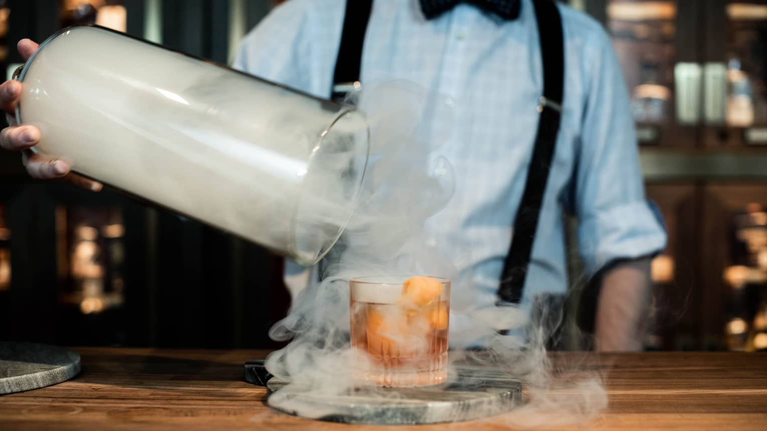 Smoke swirls around a cocktail as a bartender removes a lid