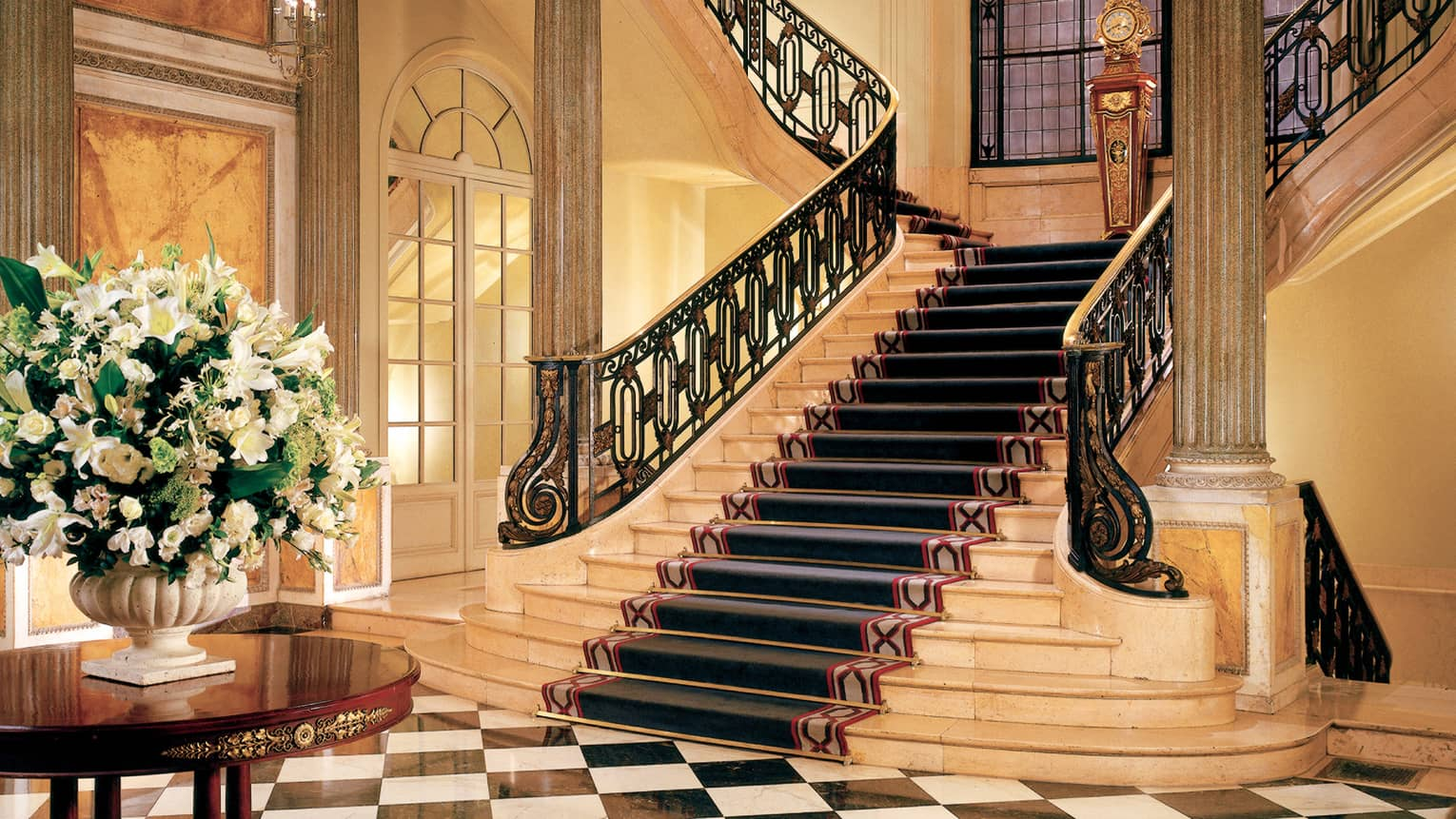 Sweeping marble staircase leading to black-and-white checkered tile floors, table with white floral display