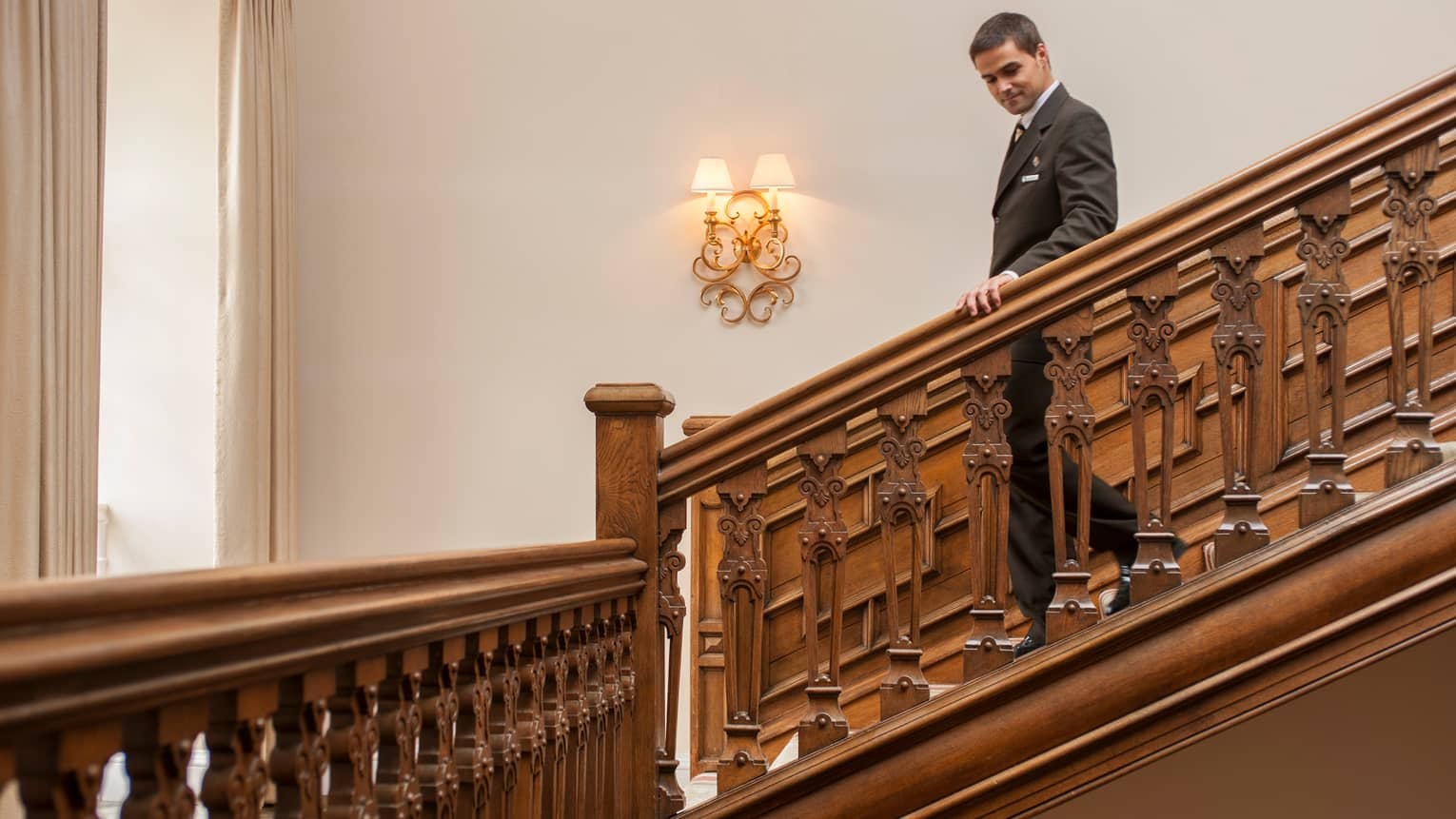 Hotel staff descends down carved  wood staircase past wall lamp