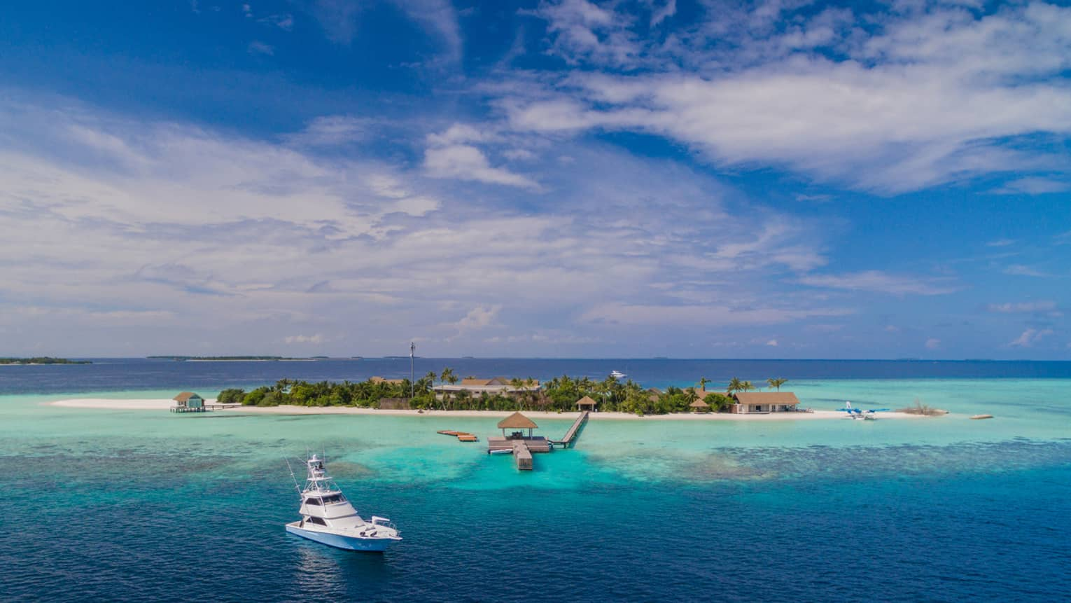 Aerial view of white yacht in lagoon near Four Seasons Maldives private island resort