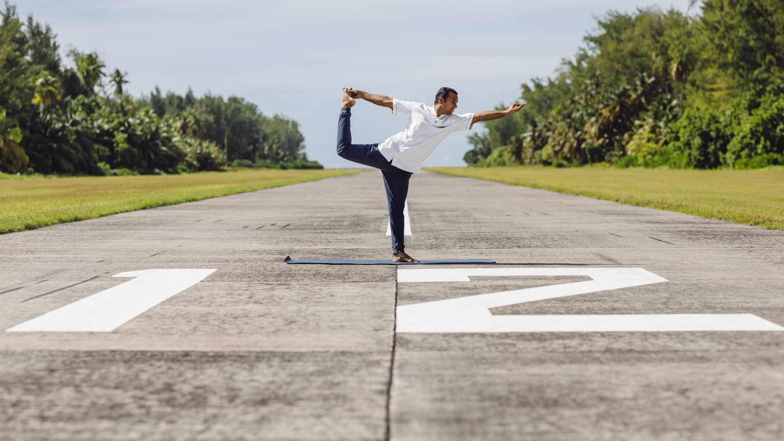 A man doing yoga – specifically ballerina pose – on an airplane runway