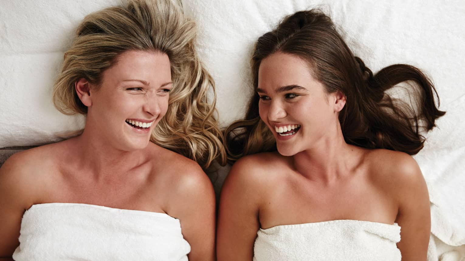 Two laughing women wearing white towels lie on massage table in spa