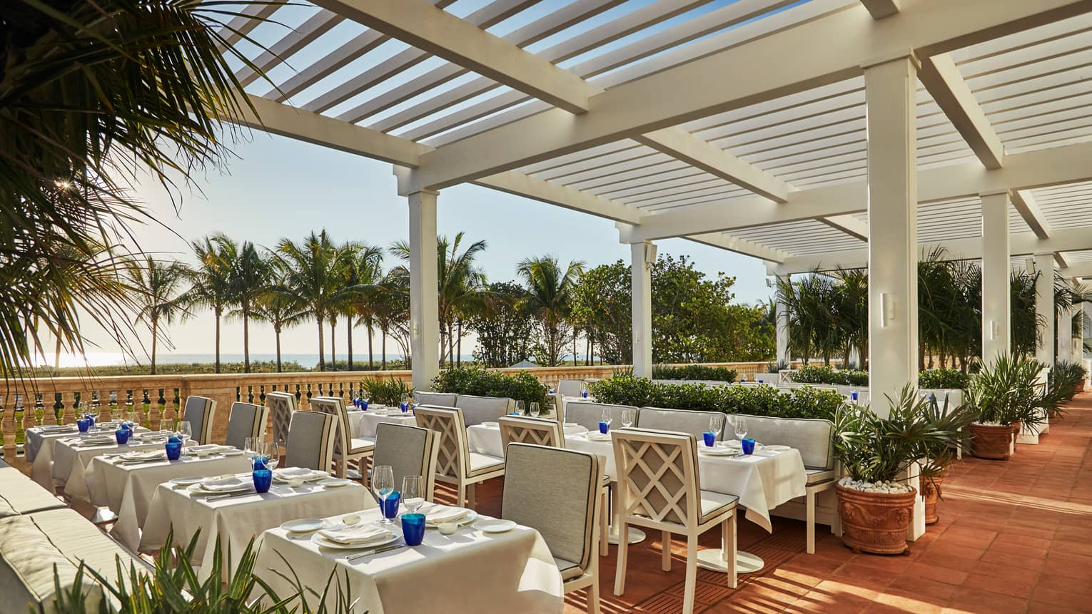 Large restaurant patio with formal dining tables under white pergola. Palm trees and beach in background