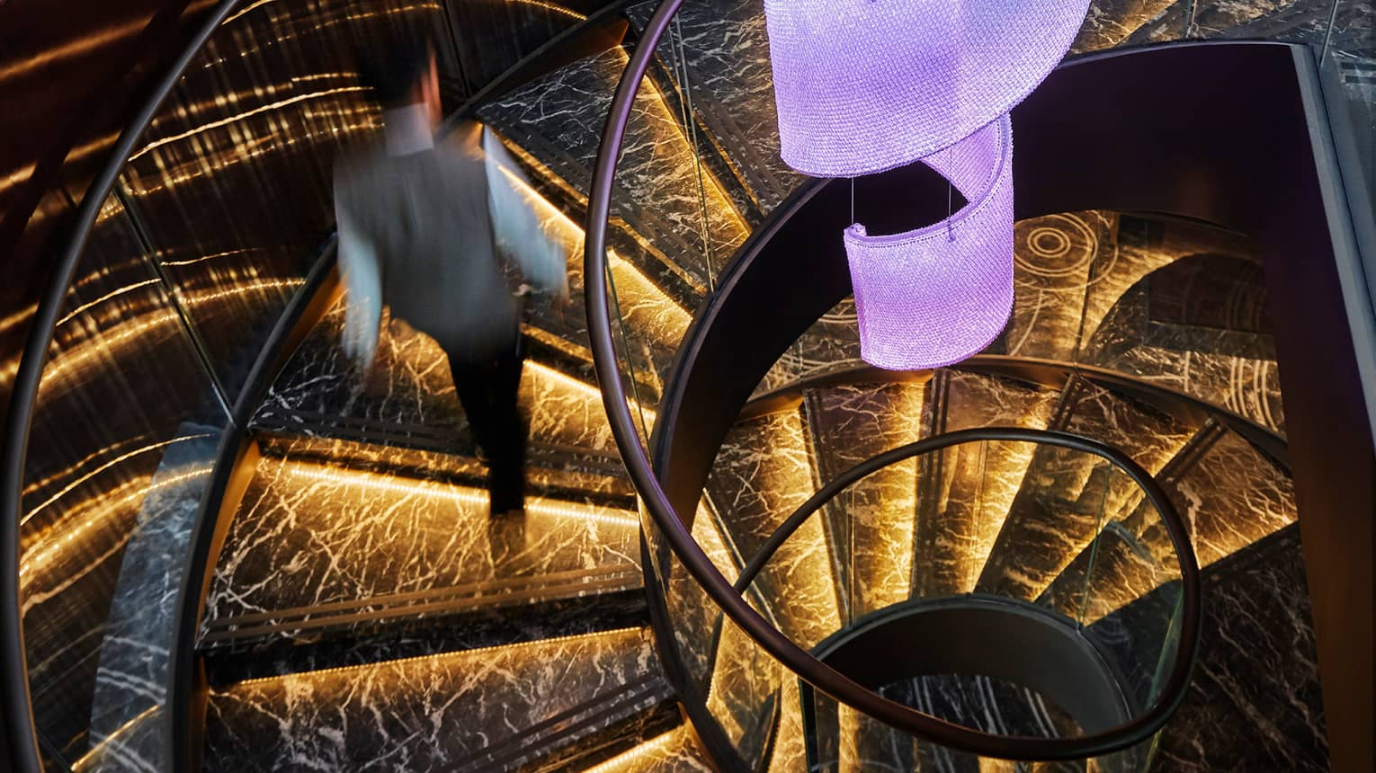 Server in uniform walks up black marble spiral staircase with orange lights