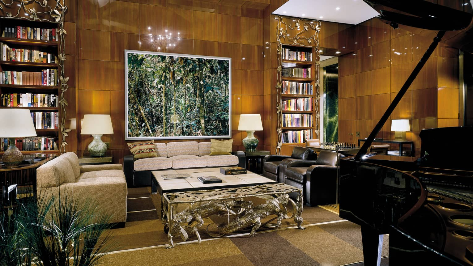 Ty Warner Penthouse grand piano, seating area, forest painting on gleaming wood panel walls, soaring ceilings