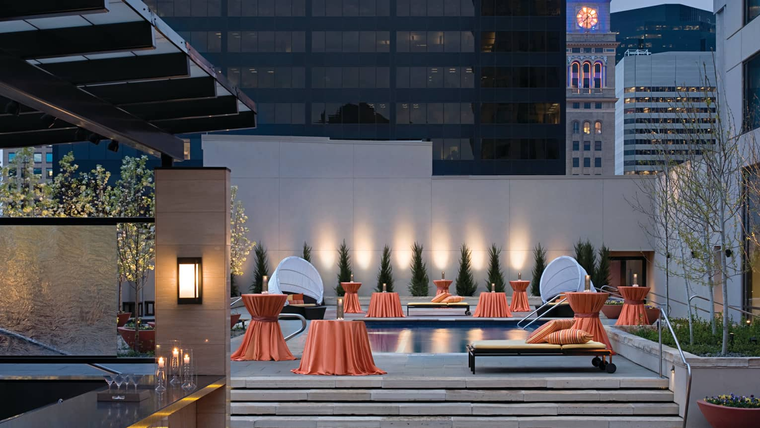 Rooftop bar, orange linens over small tables around outdoor pool