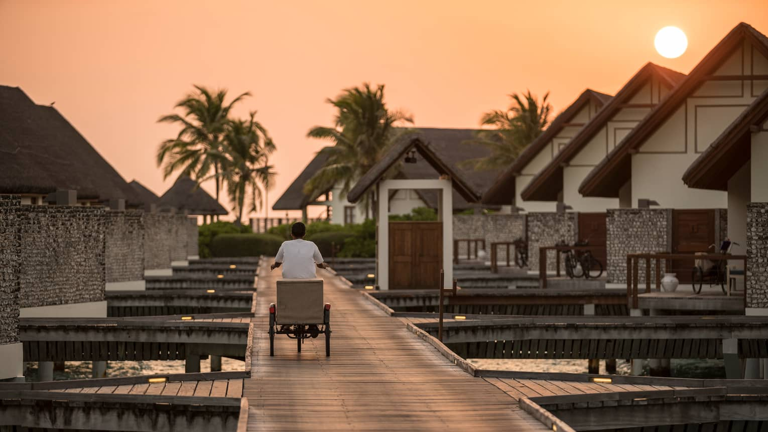 Back of man riding breakfast delivery cart along wood walkway connecting overwater bungalows at sunrise