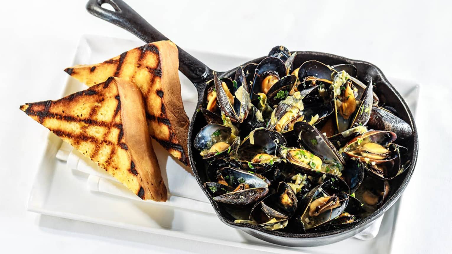 Iron pan with black steamed mussels, garlic toast