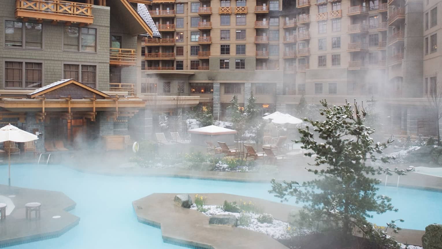 Steam rises from outdoor whirlpools over patio with light-snow covered chairs, umbrellas, trees