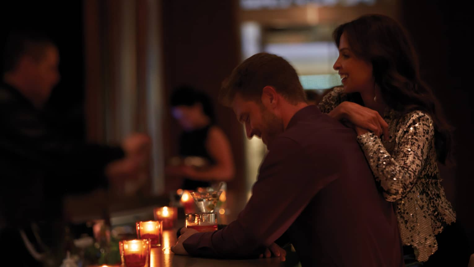 Woman in sequins blazer leans against man at candle-lit bar