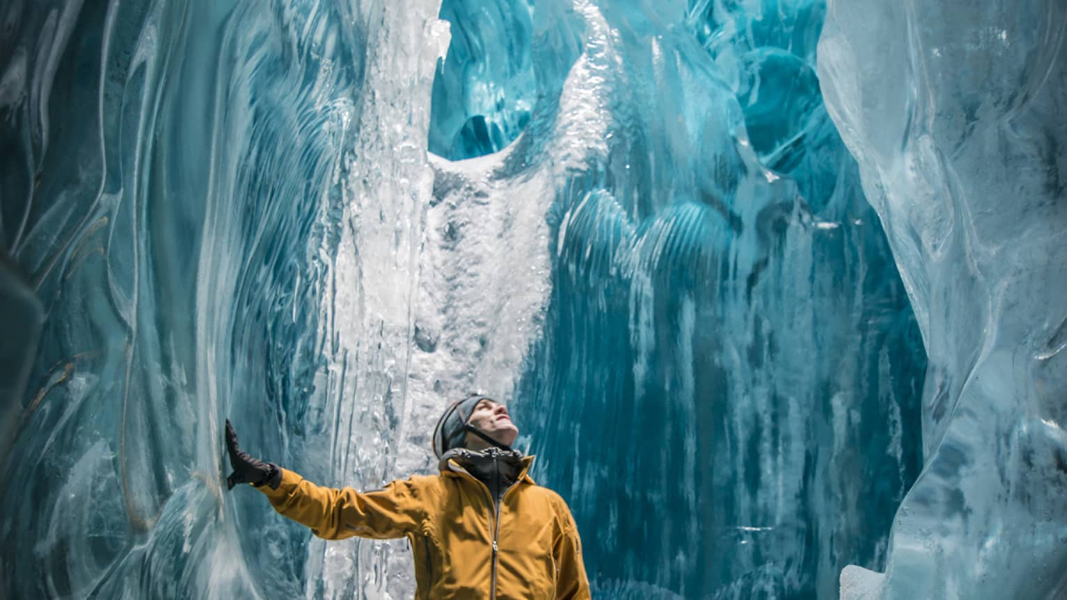 A man in a yellow winter coat explores a vast cave of translucent ice