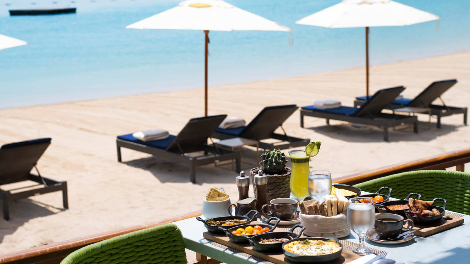 Patio dining table with breakfast items in front of sunny beach, lounge chairs
