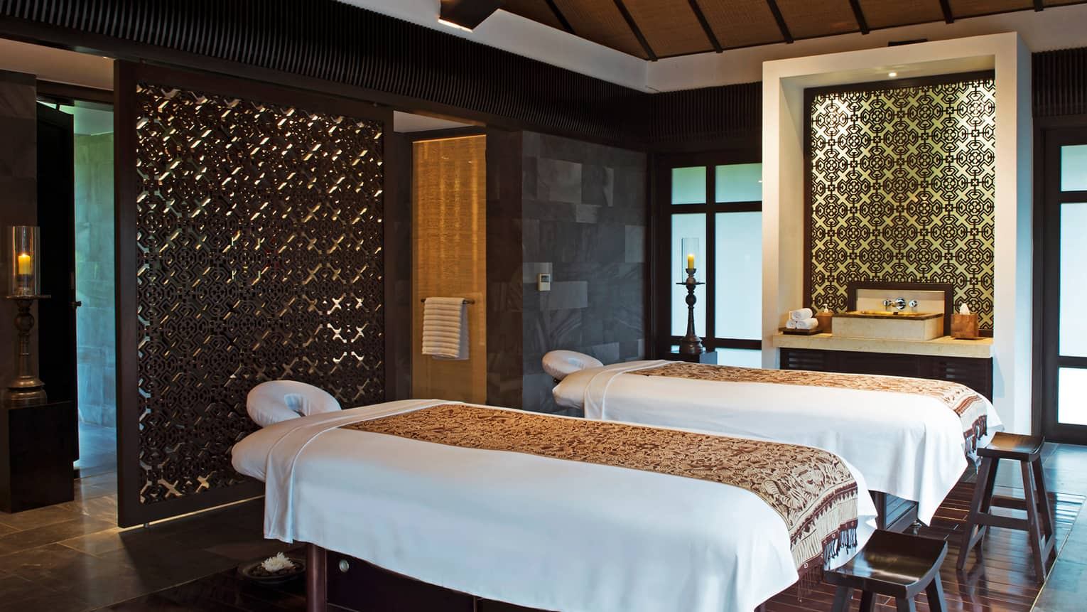 Couples massage tables side-by-side in spa treatment suite with decorative walls