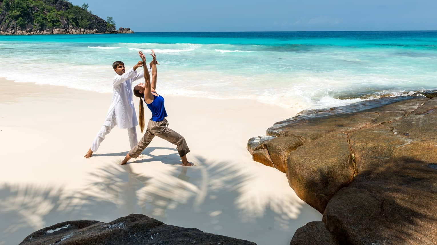 Yogi in white holds woman's arm as she does yoga pose on white sand beach by ocean