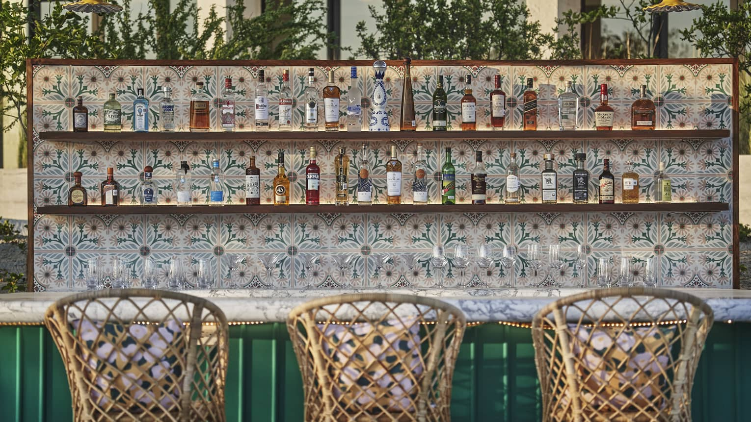 Three ratan bar stools are in front of a teal outdoor bar with bottles of liquor sitting on tiled shelves