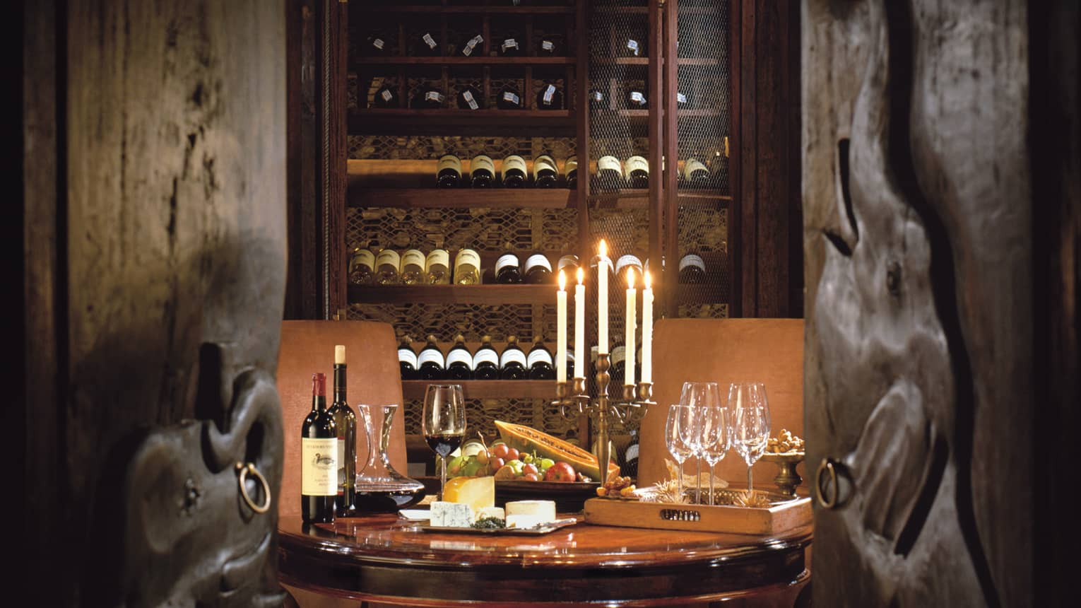 A dimly lit table for two with a candelabra and wine in a wine seller