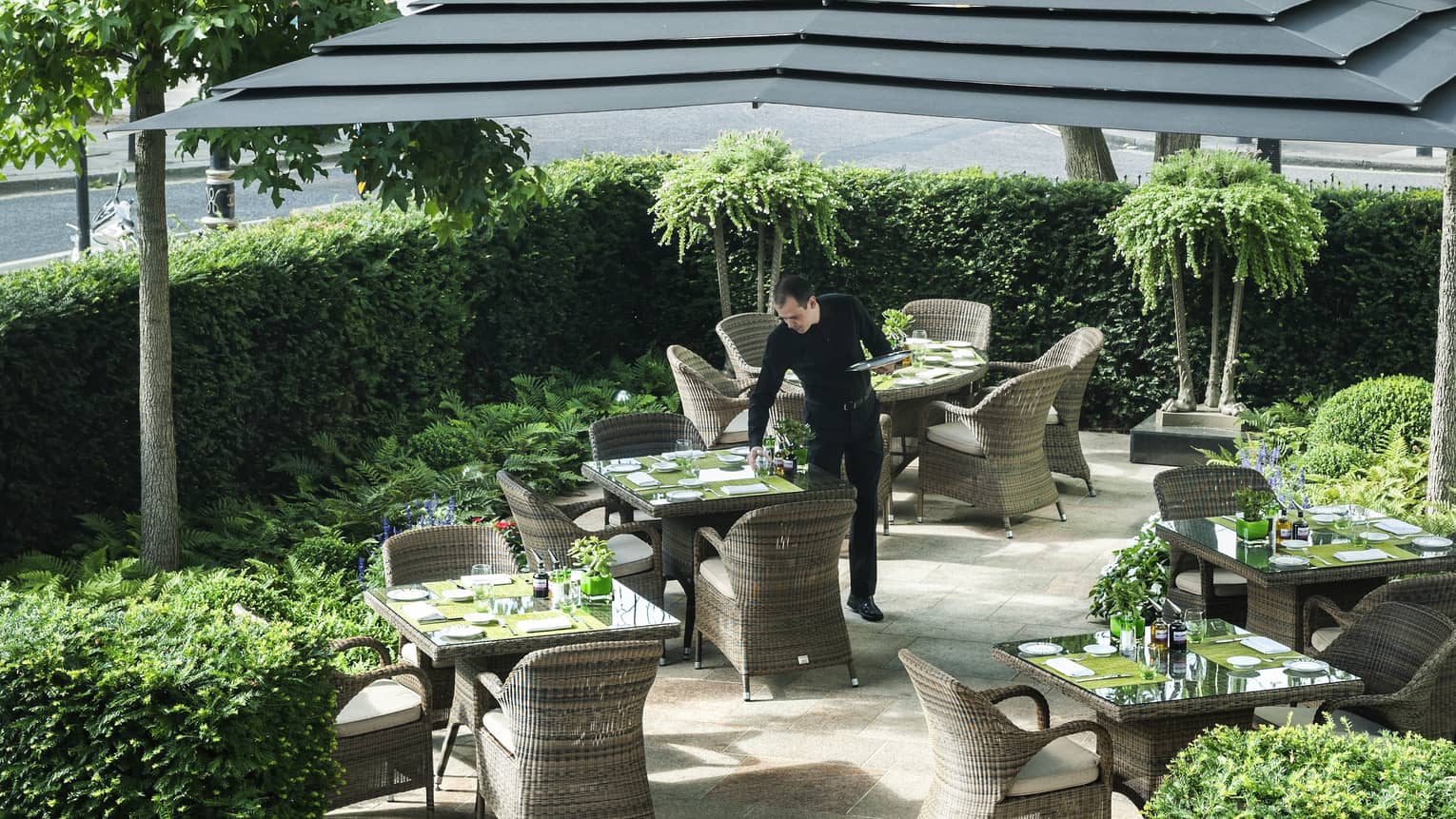 Hotel staff sets patio dining table under large umbrella