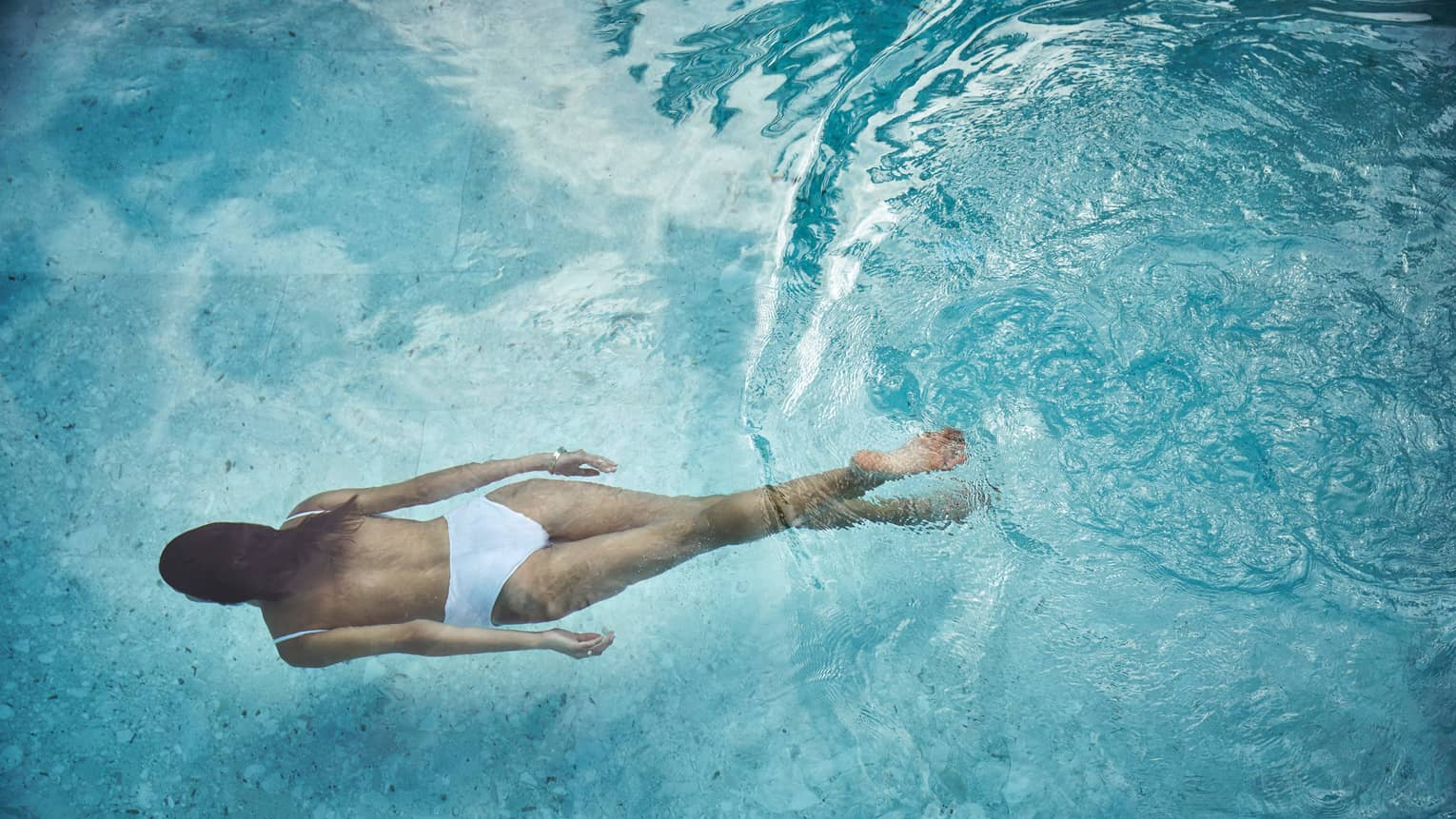 Woman in white swimsuit swimming underwater in blue pool