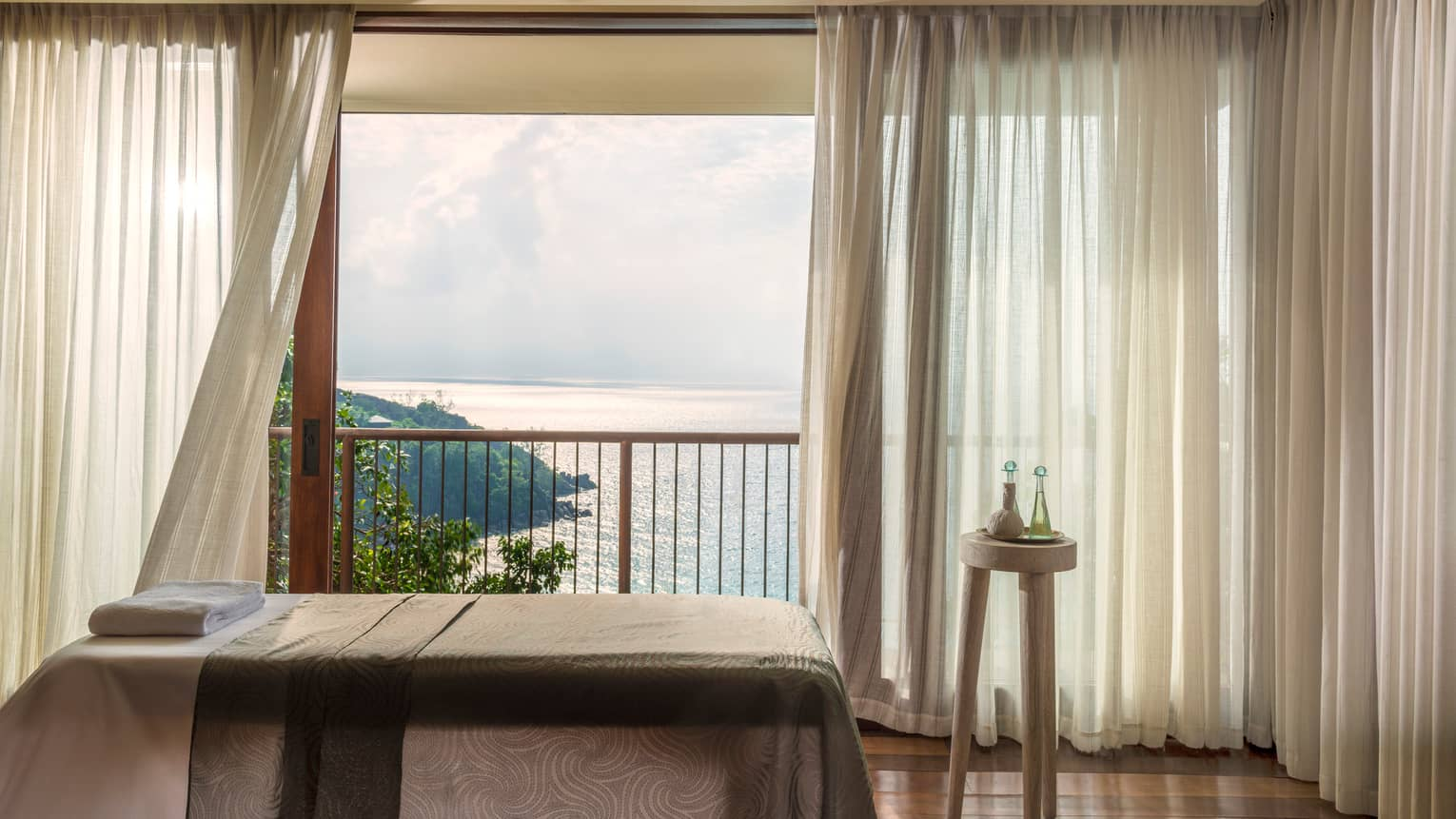 Massage bed in front of open window with long white curtains, ocean view