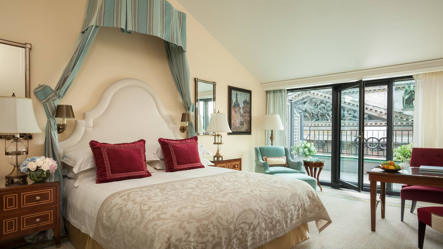Terrace Room bed with red accent pillows under striped green and blue canopy, large window