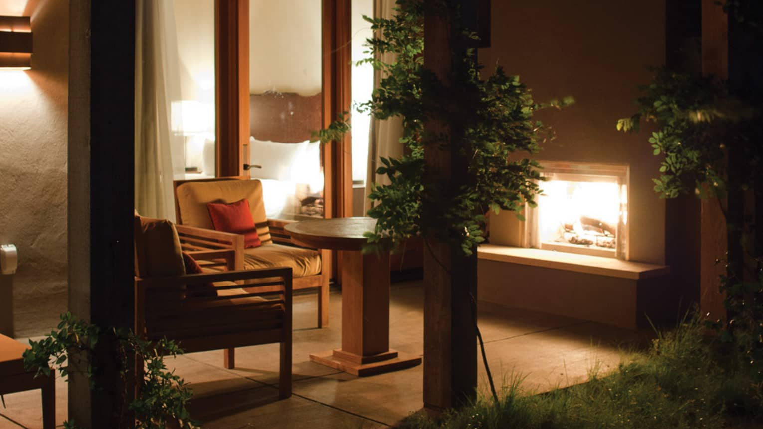 Casita patio chairs, wood beams, outdoor fireplace at night