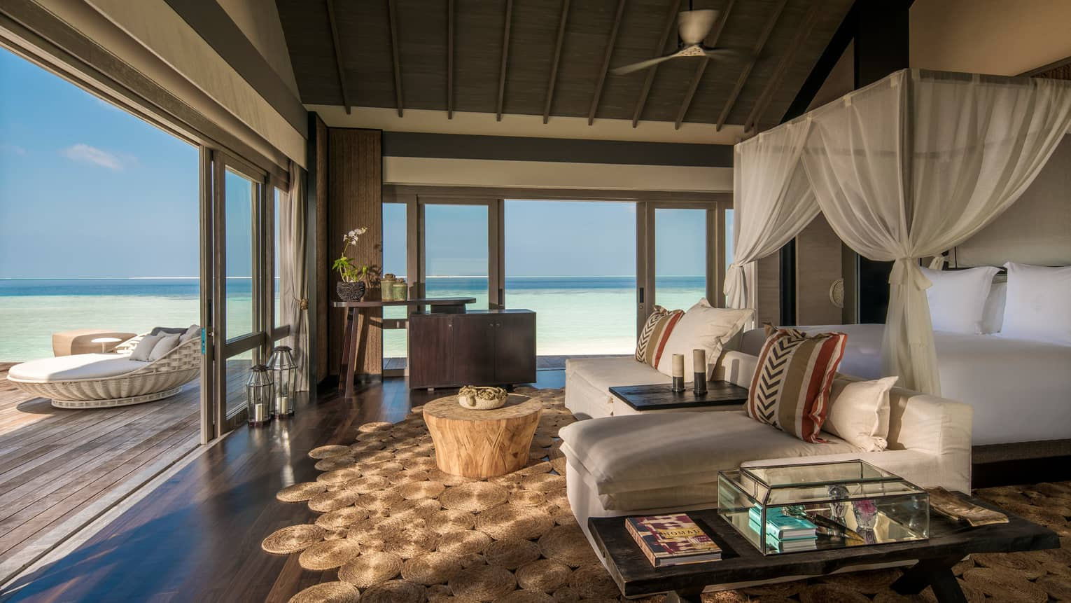 Three-Bedroom Beach Villa canopy bed. chaise lounge chairs across from open sliding doors to patio