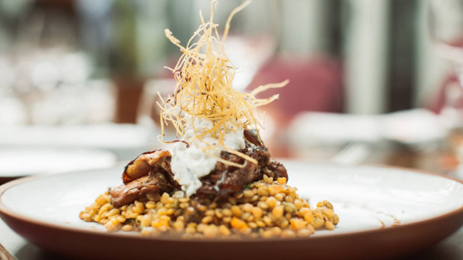 Braided lamb is served on top of Turkish lentils and topped with crispy onion