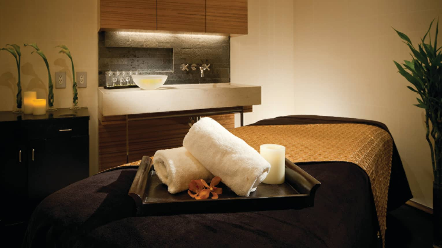 Spa treatment room, bamboo tray with towels, candles, flower on massage bed