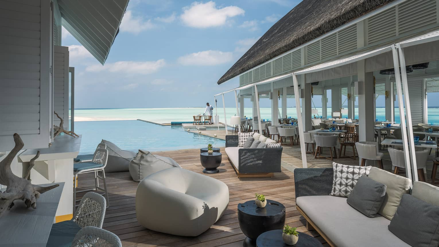 Couches and chairs arranged by a pool overlooking the ocean at the Blu Beach Club
