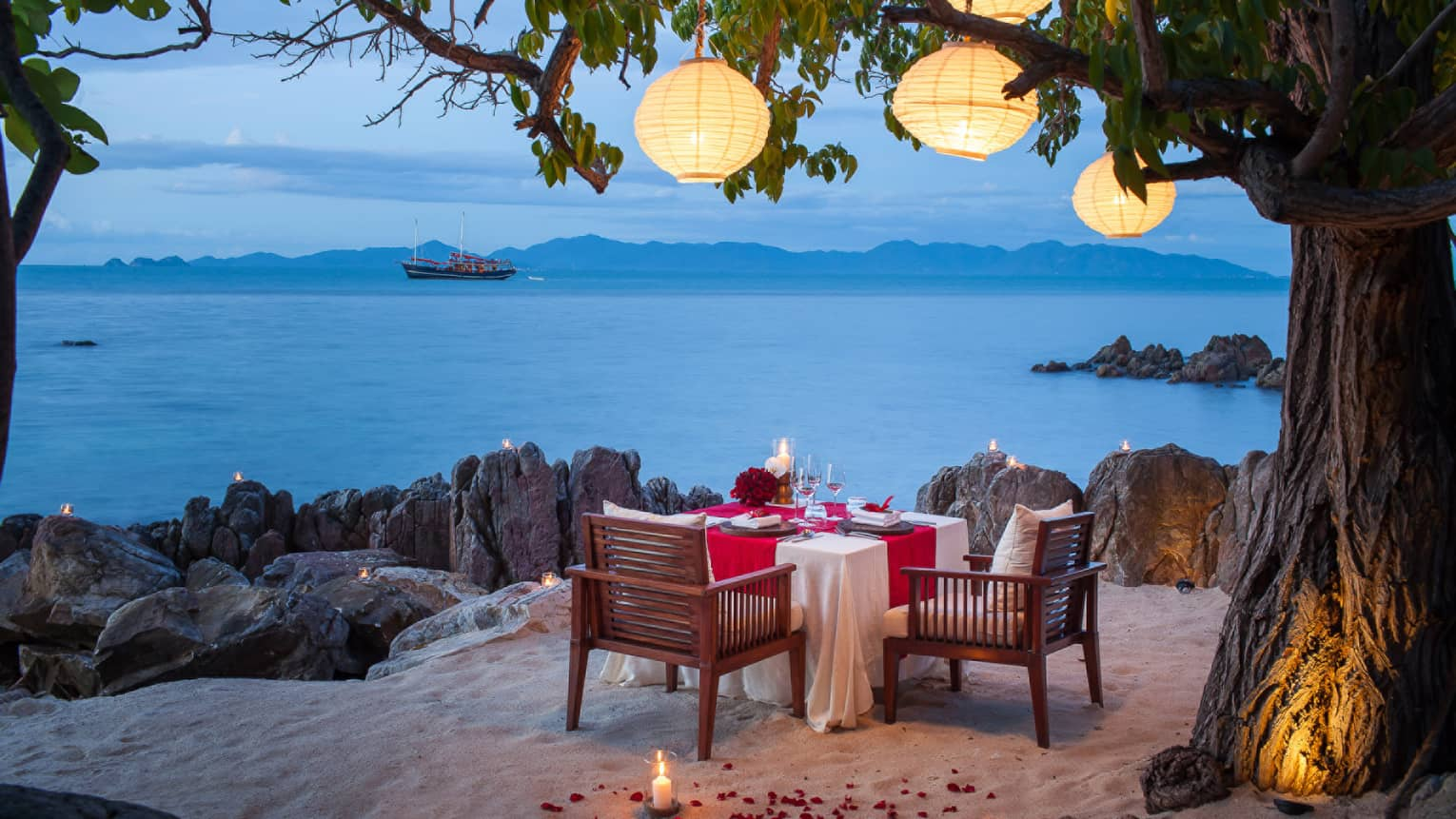 Private dining setting on the beach with a view of the Gulf of Thailand
