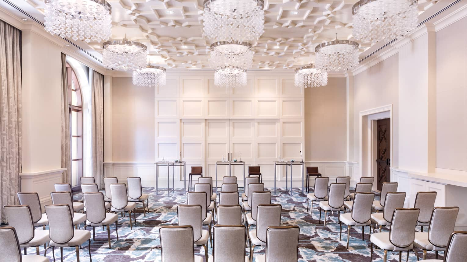 A cream colored function room is set up with rows of neutral chairs lined up and facing three tables in the front