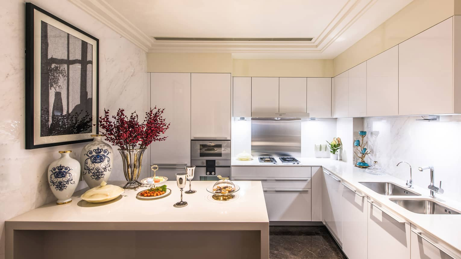 Kitchen with white cabinets, island counter with serving trays, wine glasses, vases and flowers