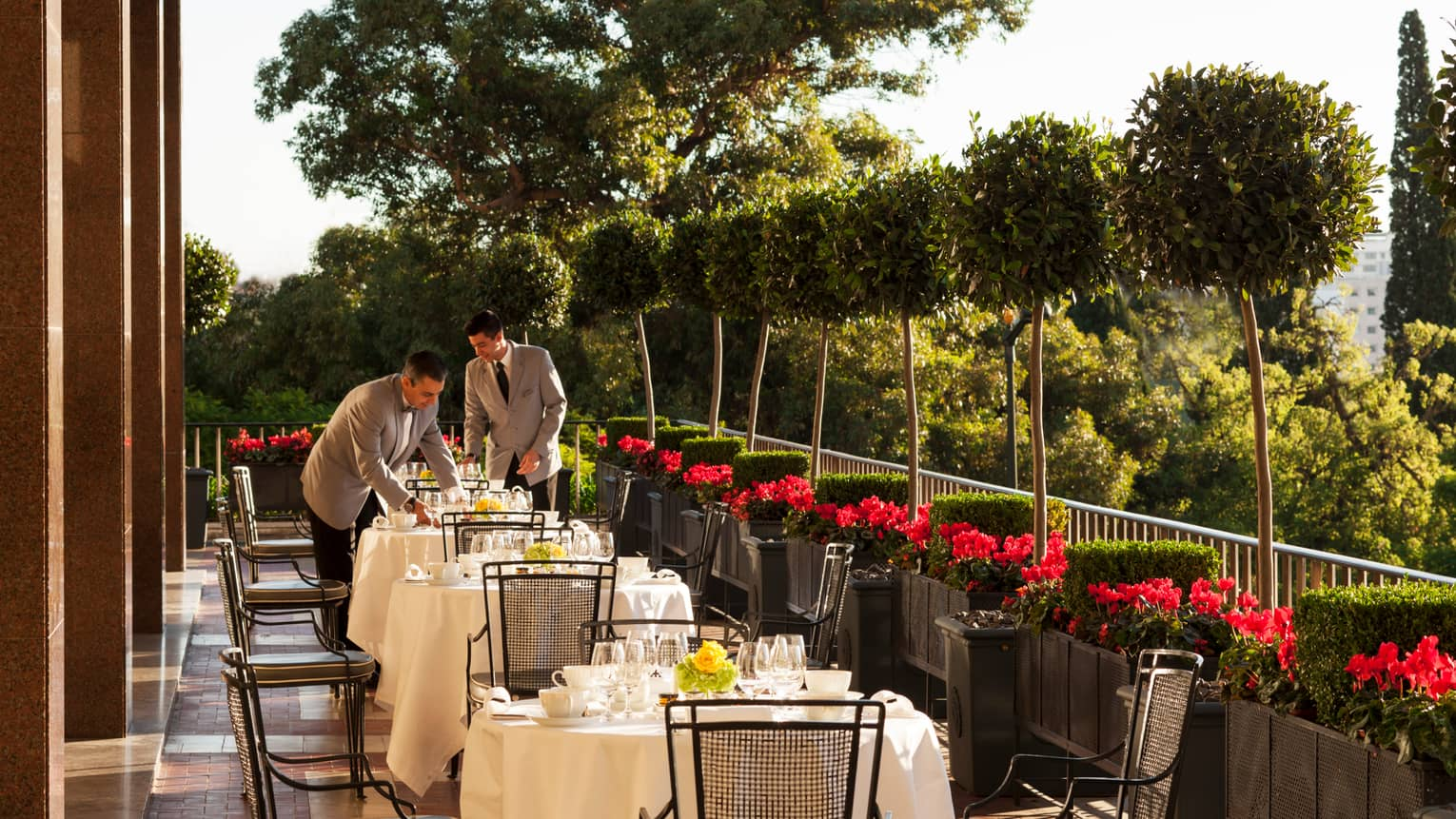 Two servers in grey jackets with black ties set outdoor dining tables with white tablecloths, dishes, red flowers along side