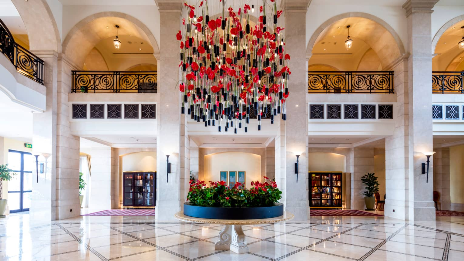 Art piece with red flowers, stems with black caps hangs from two-storey lobby ceiling, white tiles, iron balconies