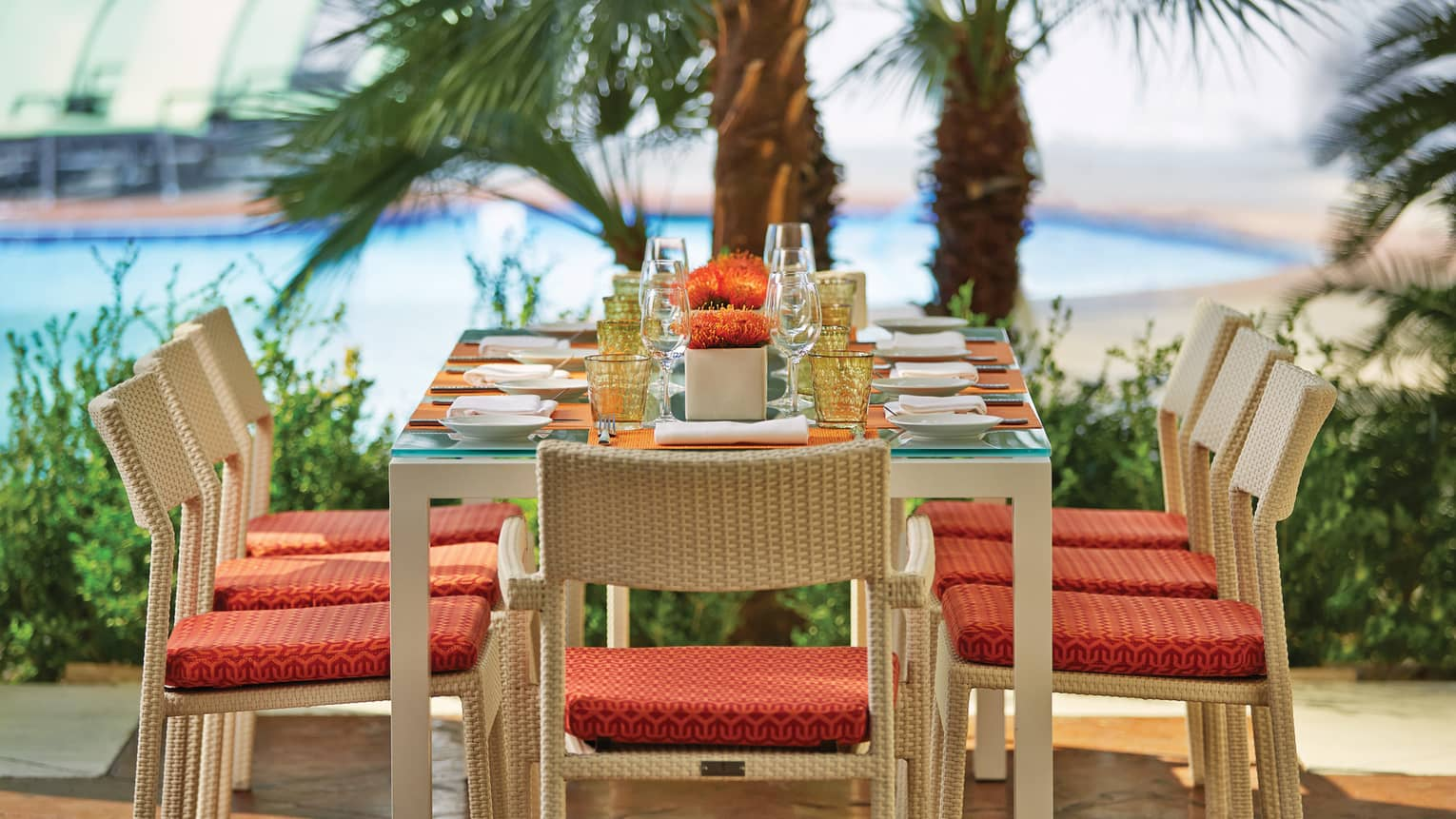Veranda Restaurant patio dining table, chairs with red cushions, palms in background
