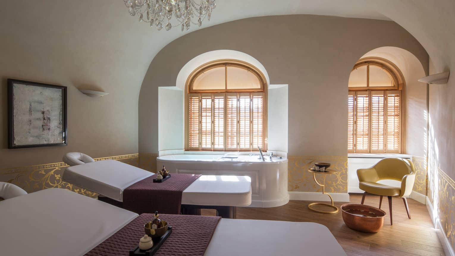 Two white beds beside spa tub in dimly-lit room at the Vltava Suite at AVA Spa
