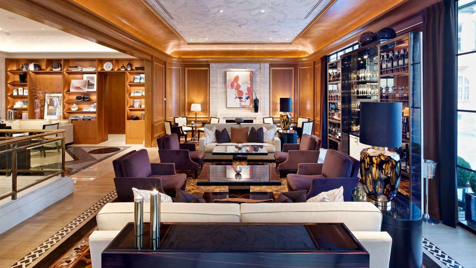 The Gallery bar and lounge with clusters of purple sofas, white armchairs, wall with wine and liquor bottles