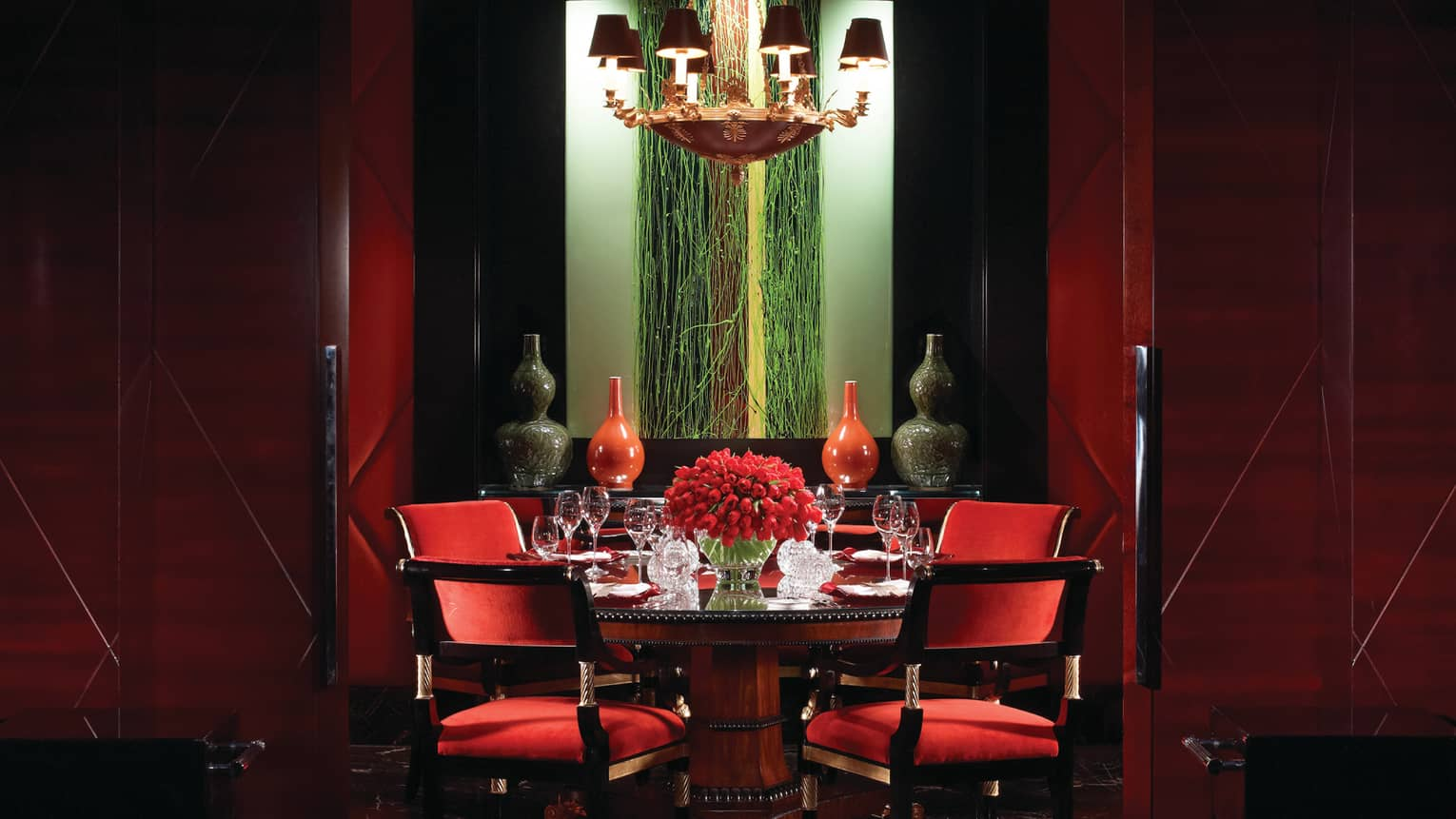 Amaranto restaurant red velvet chairs around round dining table with red tulips, red and black vases