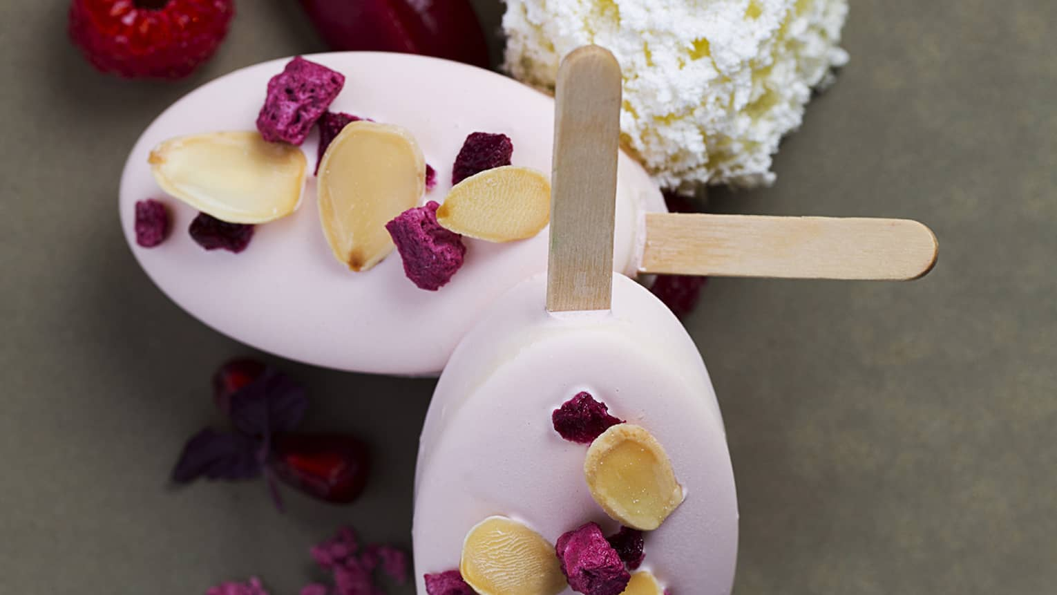 Two pink popsicles lay crossed on a plate garnished with raspberries and pomegranate seeds