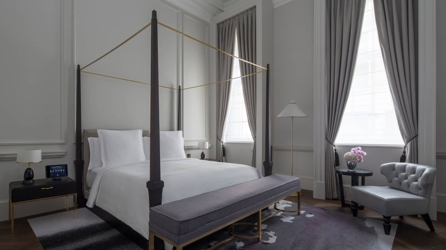 Grand Heritage Suite bed with canopy bed, padded bench, high ceilings, white walls with original columns