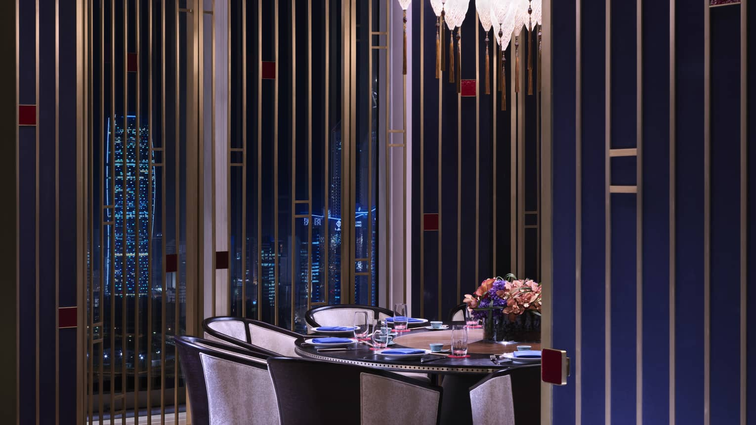 Elegant round dining table, chairs under small crystal light in front of window with city views at night
