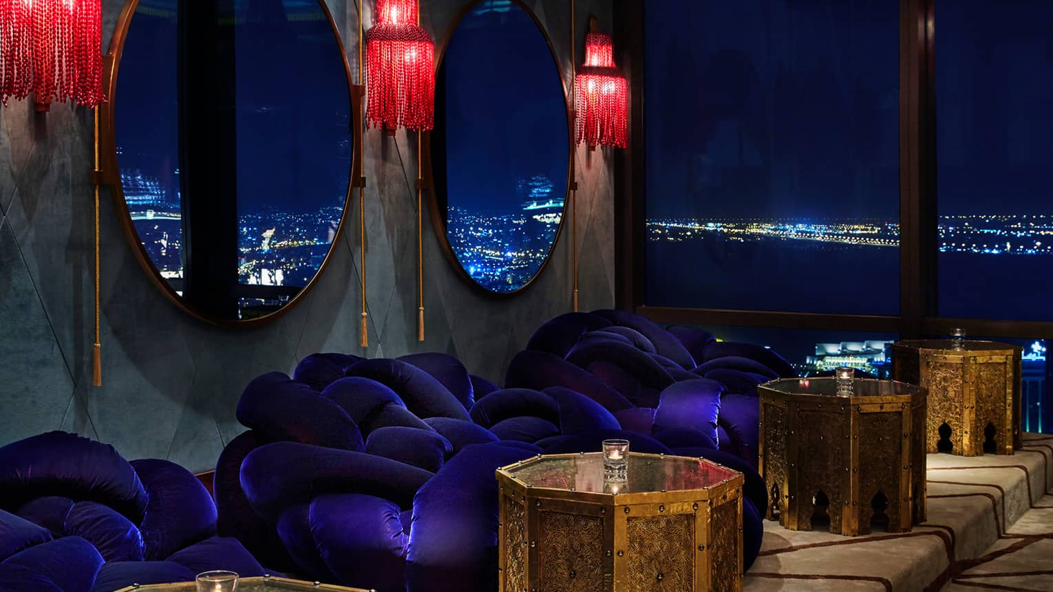 Close-up of blue velvet plush round chairs under red lamps, mirrors, gold tables, city lights