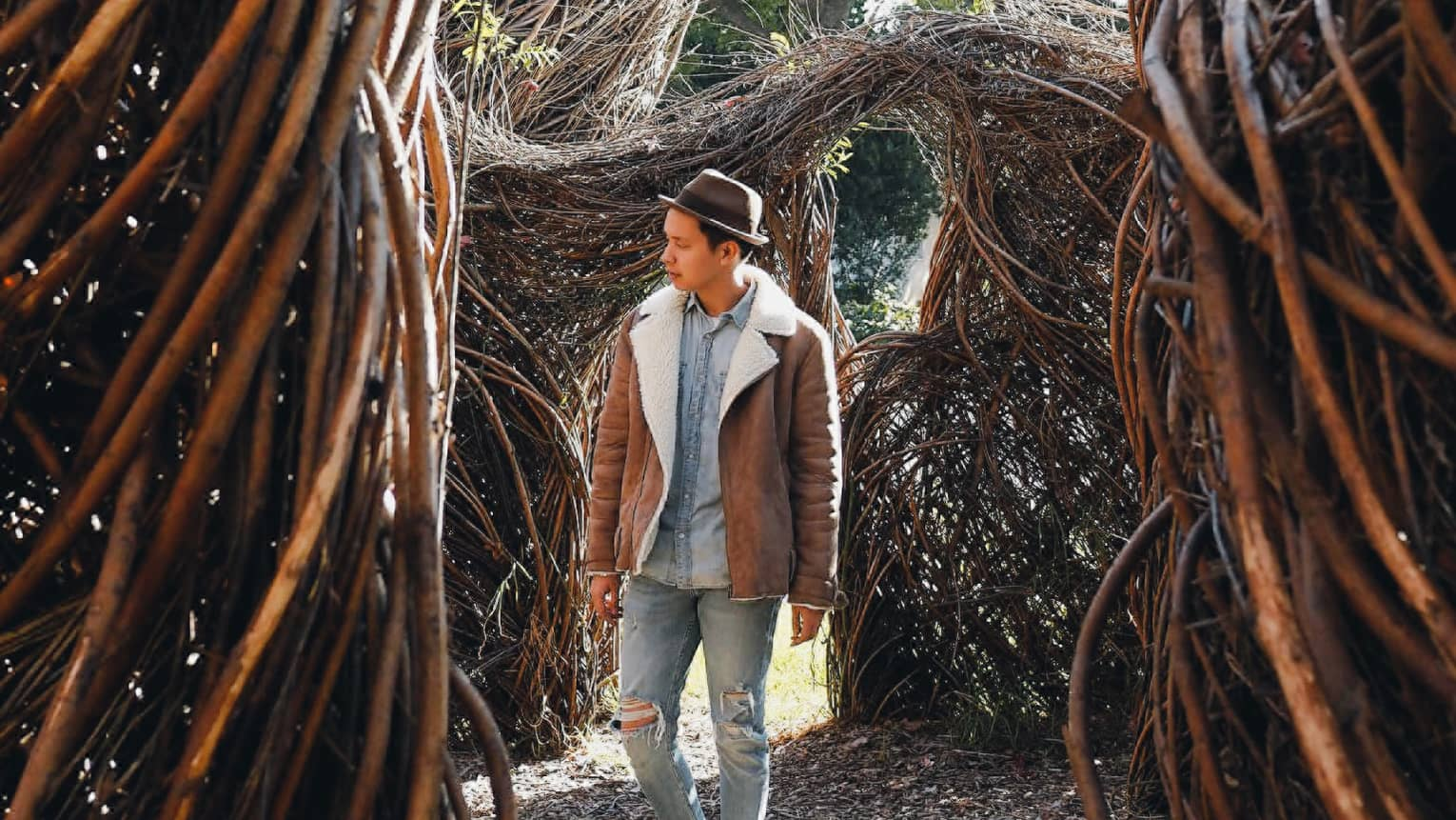 Man in shearling coat, fedora hat walks through twisted branches, trees