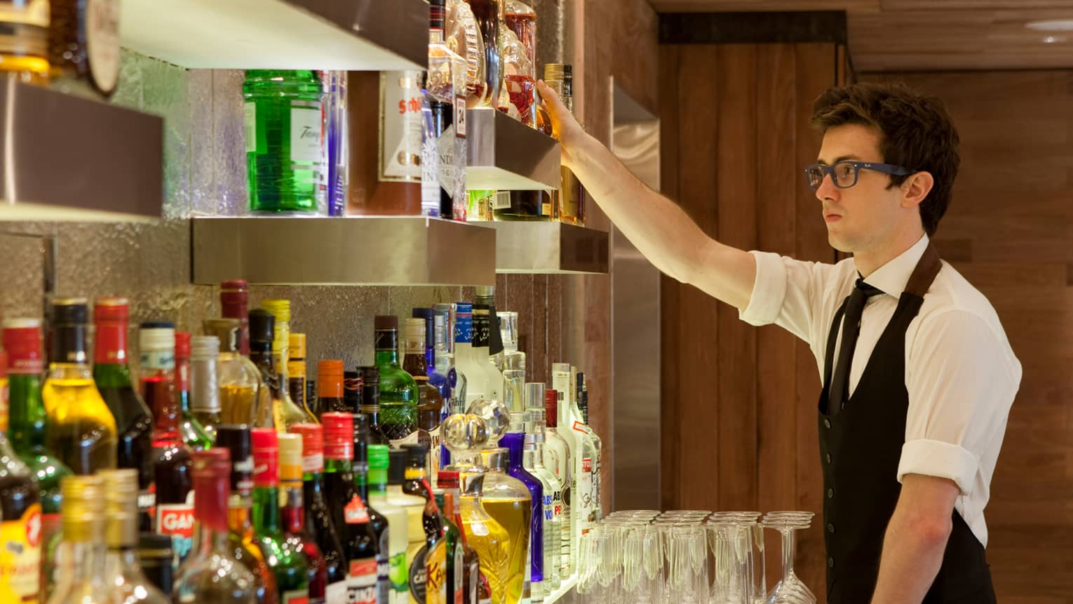 Pony Line bartender in white shirt, black vest, glasses reaches for a bottle on liquor display shelf