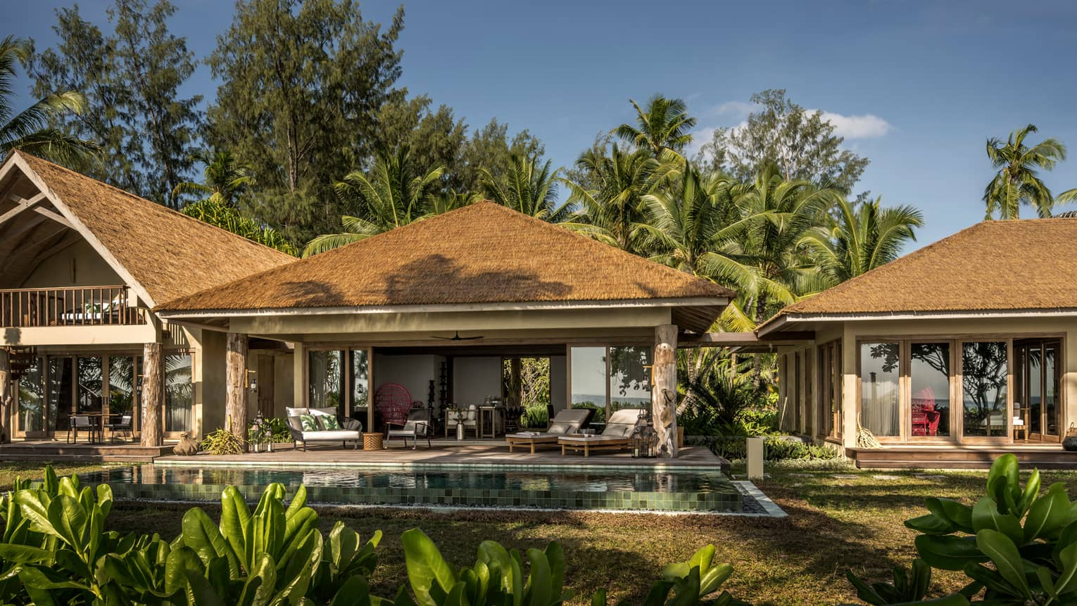 Airy tropical accommodations surrounded by palm trees, with plunge pools