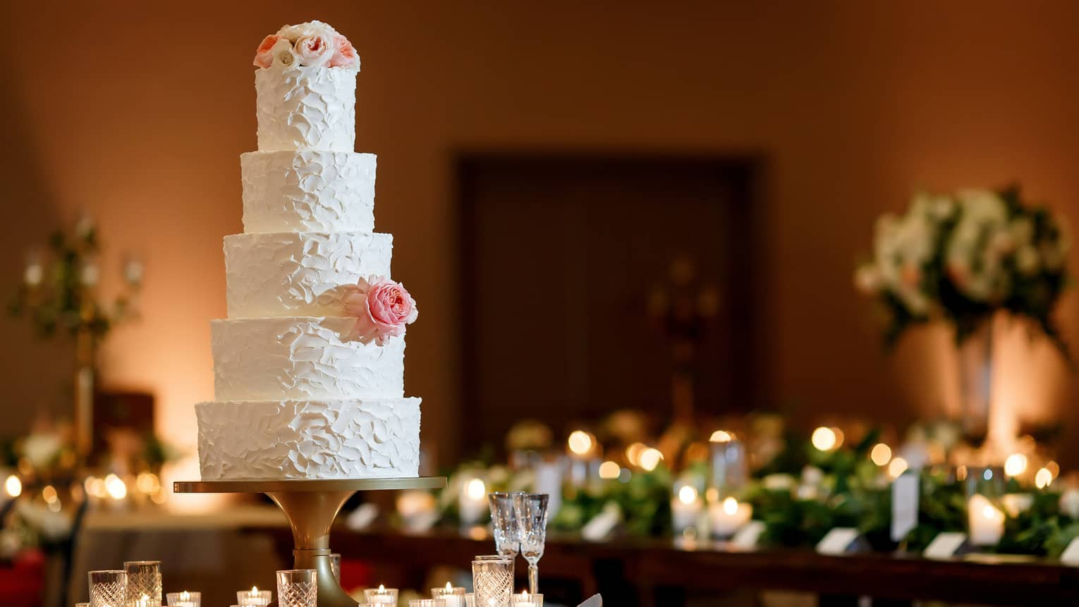 A five-tiered white wedding cake garnished with a white rose and some small white and pink flowers on the top tier , sits on a white round table surrounded by white candles