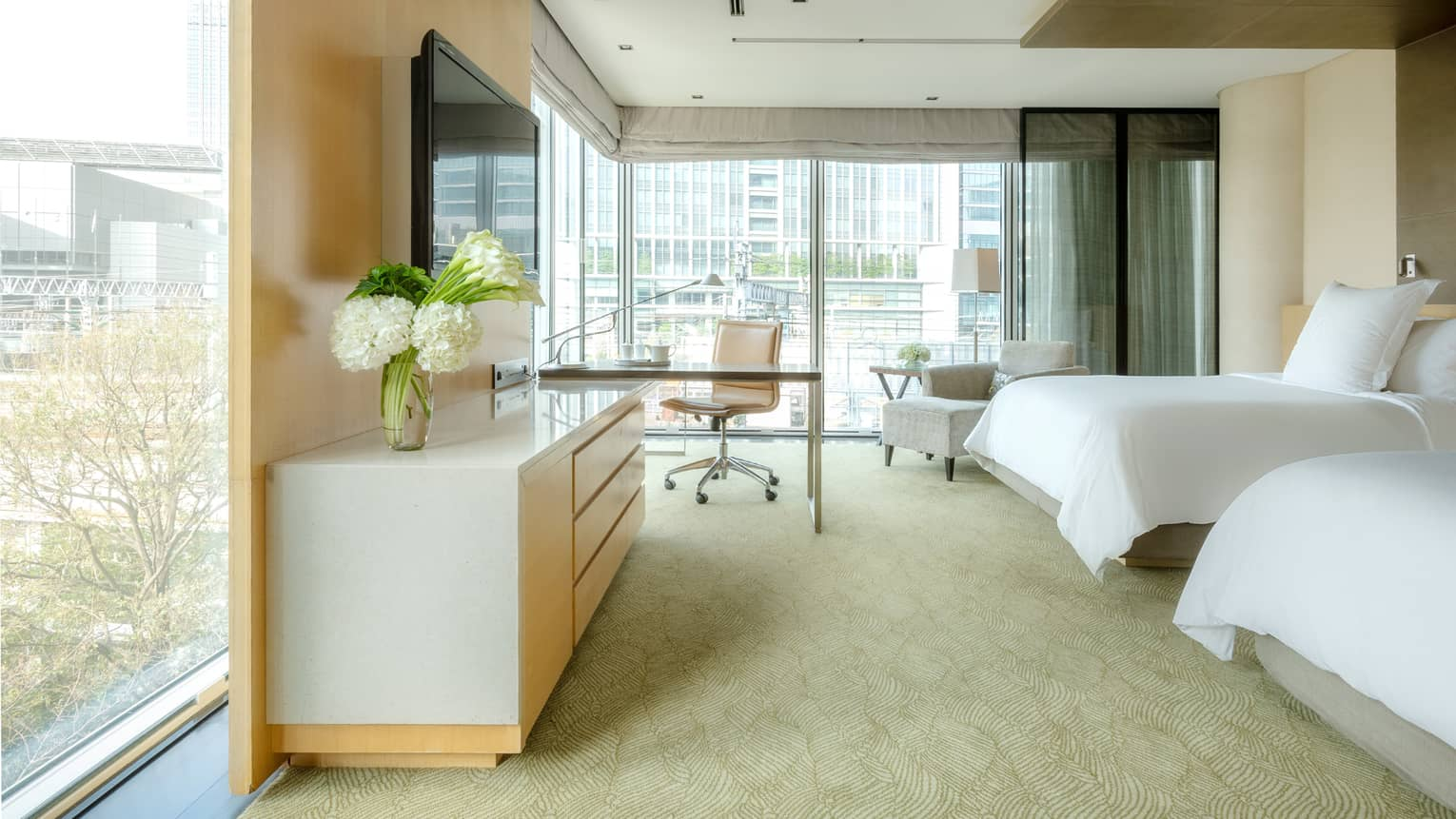 Deluxe Premier Twin Room with desk area and floor-to-ceiling corner windows looking out onto the city skyline