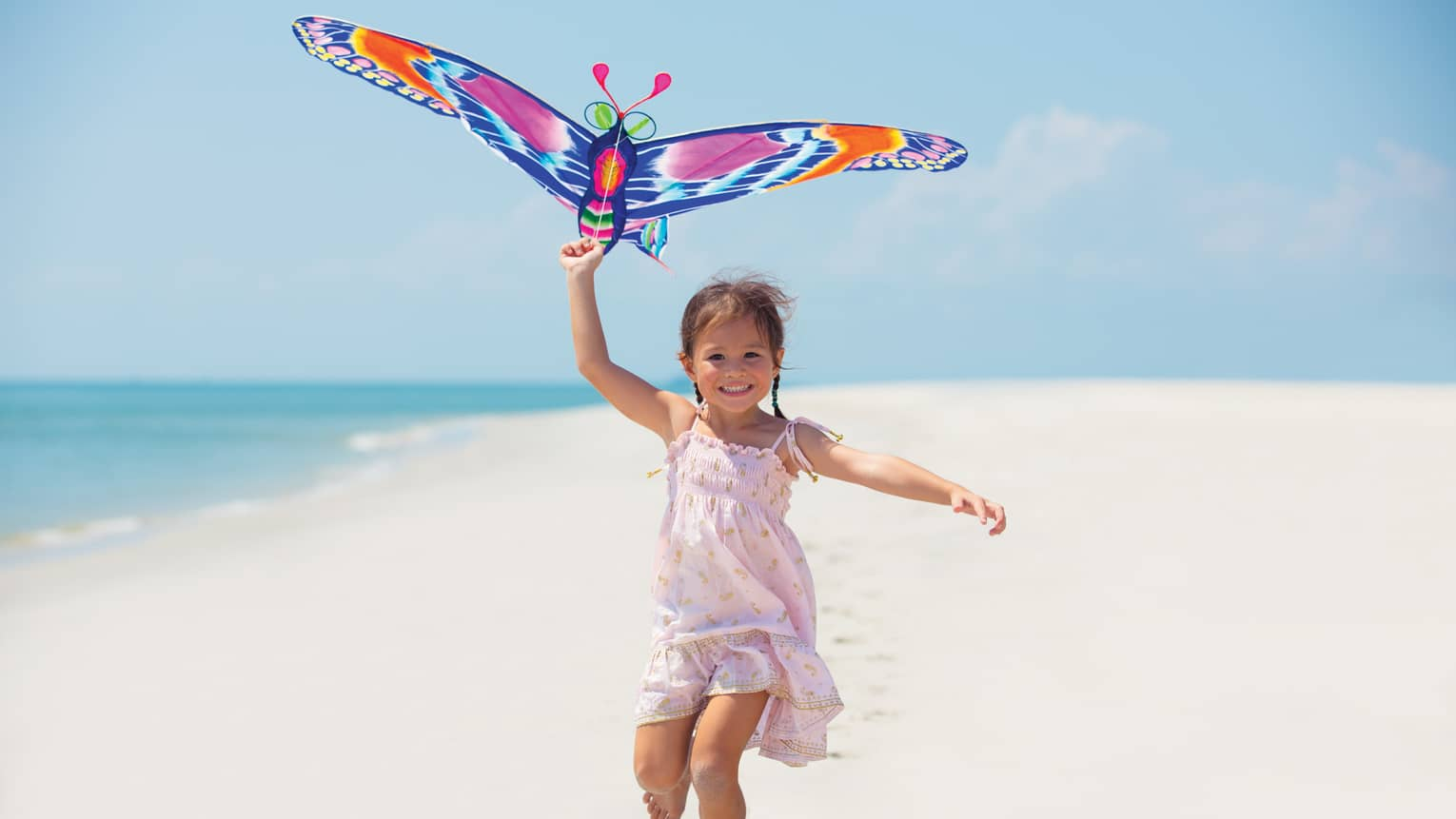 Young girl runs with colourful butterfly kite on white sand beach