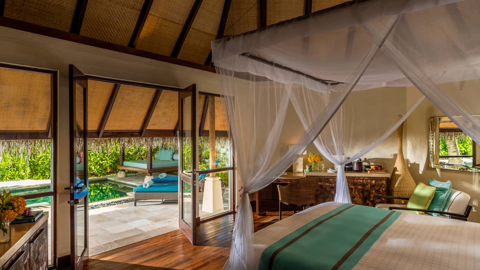 Traditional beach pavilion suite with canopy bed and open-air doors and windows leading to patio